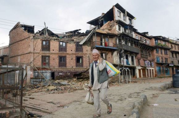 a man walking along a street near a collapsed house following an earthquake May 1, 2015 Photo by Navesh Chitrakar