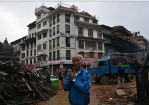 A Nepalese resident performing a morning prayer near a temple in the earthquake-damaged Durbar Square in Kathmandu on April 30, 2015. Photo by Prakash Mathema